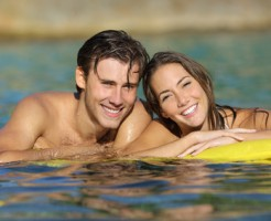 Happy couple bathing on the beach in summer vacation