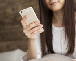 Young women are using a smart phone in the room