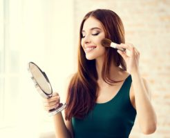 Young woman with mirror and makeup brush indoors. Beautiful caucasian model in make up and beauty treatment concept shoot.